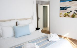 The Leto Villa in Mykonos spacious bedroom with double bed and modern decor.