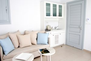 The Leto Luxury Villa in Mykonos sitting rooms with sofa, two coffee tables and kitchenette.