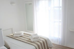 The Leto Luxury Villa in Mykonos second bedroom is brightly lit by the morning sun.