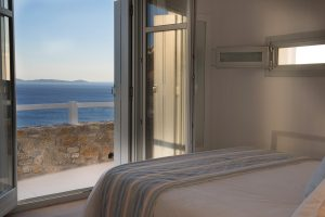 The open windows of the Leto Luxury Villa in Mykonos 2nd bedroom reveal panoramic sea views.