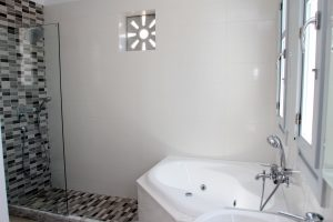Bathroom of the Artemis Luxury Villas in Mykonos. Modern design bath and shower and windows.