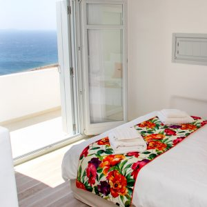 The Artemis Luxury Villa in Mykonos bedroom is brightly lit by the morning sun.