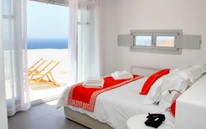 The Asteria Luxury Villa bedroom with a view of the Aegean sea, double bed and bedside table.
