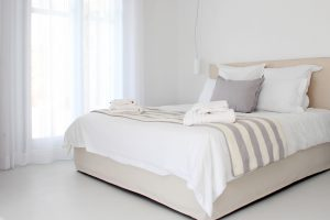 The Hera Luxury Villa in Mykonos bedroom is brightly lit by the morning sun.