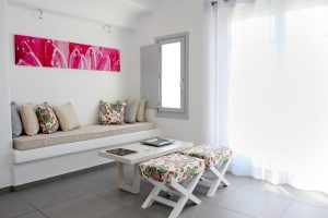 The Hera Luxury Villa sitting room includes sofa, window, coffee table, and view of the sea.