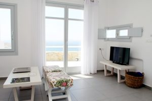 The Hera Luxury Villa sitting room with view of the sea, coffee table, flat screen TV and stools.