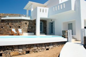 View of the Hera Luxury Villa and the villa swimming pool with two sun beds.