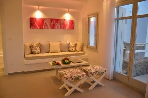 The Hera Luxury Villa in Houlakia, Mykonos sitting area with sofa, table and stools.