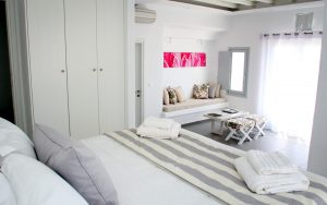 The luxury Hera Villa in Houlakia, Mykonos offers a brightly lit spacious sleeping and sitting area.