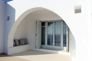 Archway outside sitting area and large windows facing the Aegean sea.